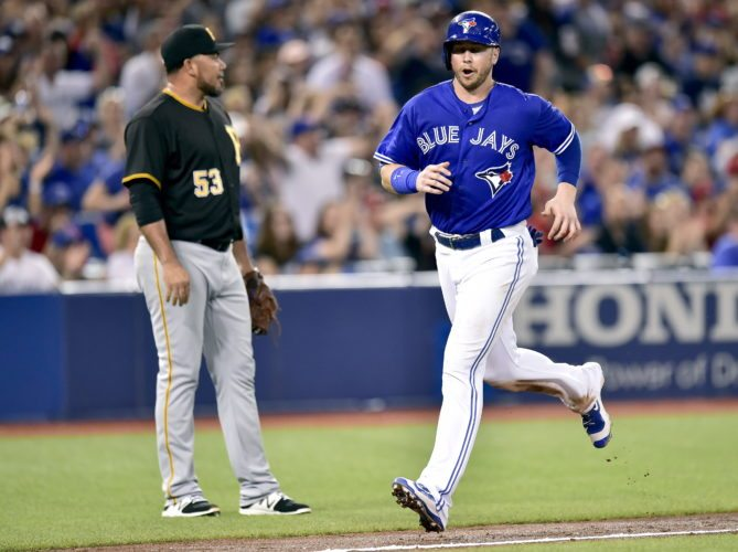 Pittsburgh Pirates relief pitcher Joaquin Benoit (53) looks on as Toronto Blue Jays first baseman Justin Smoak (14) runs in to score on a wild throw during seventh inning baseball action in Toronto on Saturday, Aug. 12, 2017. (Frank Gunn/The Canadian Press via AP)