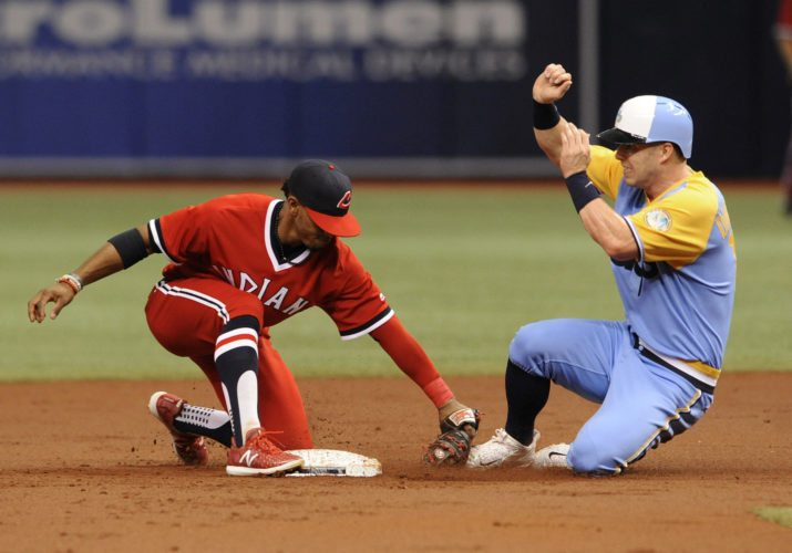 Cleveland Indians shortstop Francisco Lindor tags out Tampa Bay Rays' Corey Dickerson to complete a double play that started with a grounder to first by Lucas Duda during the first inning of a baseball game Saturday, Aug. 12, 2017, in St. Petersburg, Fla. Both teams are wearing throwback jerseys. (AP Photo/Steve Nesius)