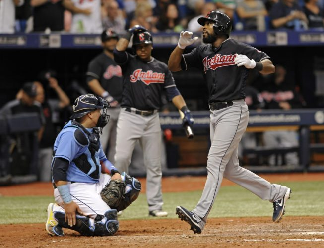 Cleveland Indians on-deck batter Jose Ramirez, center, watches as Austin Jackson runs by Tampa Bay Rays catcher Jesus Sucre, left, after Jackson hit a solo home run off Tampa Bay reliever Tommy Hunter during the eighth inning of a baseball game Sunday, Aug. 13, 2017, in St. Petersburg, Fla. (AP Photo/Steve Nesius)