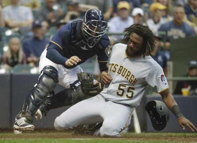 Milwaukee Brewers catcher Manny Pina tags out Pittsburgh Pirates' Josh Bell at home during the fourth inning of a baseball game Tuesday, Aug. 15, 2017, in Milwaukee. (AP Photo/Morry Gash)