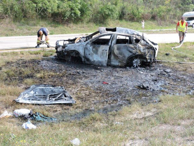 Photo by Jennifer Compston-Strough The charred remains of a car sit in the median of Interstate 70 just east of Morristown following a fiery rollover crash Wednesday morning.