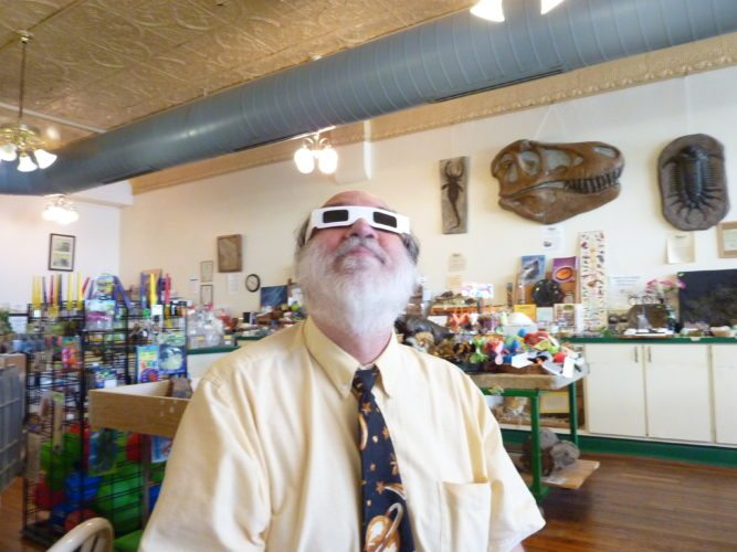 Photo by Linda Comins Astronomer Robert Strong of SMART Centre Market in Wheeling demonstrates Eclipse Shades, a special form of eye protection necessary for safe viewing of Monday's solar eclipse.