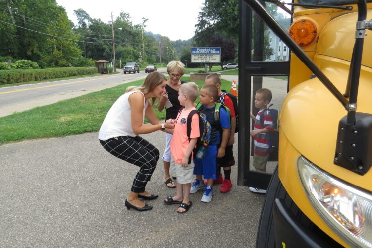 Photo Provided Woodsdale Elementary School Principal Ashlea Minch, left, and teacher's assistant Nancy Schell greet students as they arrive for the first day of school on Thursday.