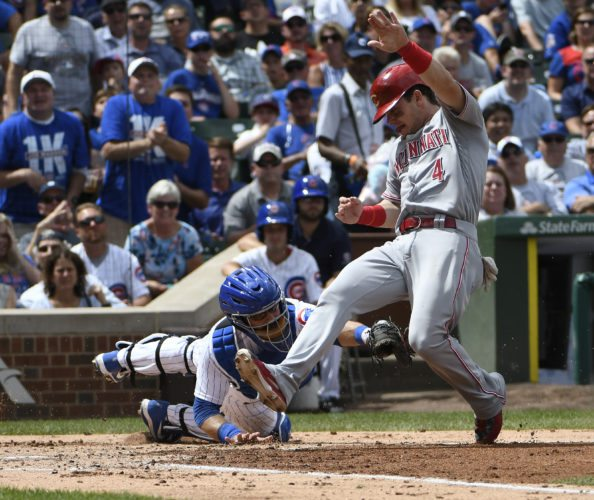Chicago Cubs catcher Alex Avila (13) misses the tag on Cincinnati Reds' Scooter Gennett (4) at home plate as Gennett misses stepping on home plate during the second inning of a baseball game, Thursday, Aug. 17, 2017, in Chicago. Avila tagged out Gennett moments later. (AP Photo/David Banks)