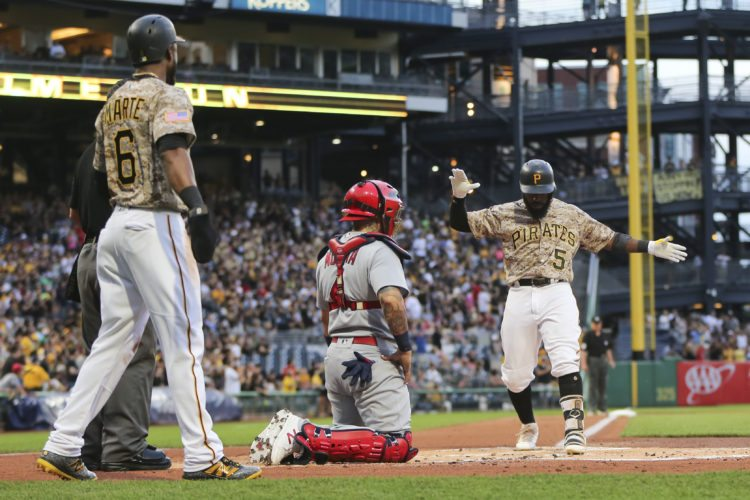 Pittsburgh Pirates' Josh Harrison (5) celebrates as he crosses home plate in front of St. Louis Cardinals catcher Yadier Molina, center, after driving in Starling Marte (6) with a two-run home run in the first inning of a baseball game, Thursday, Aug. 17, 2017, in Pittsburgh. (AP Photo/Keith Srakocic)
