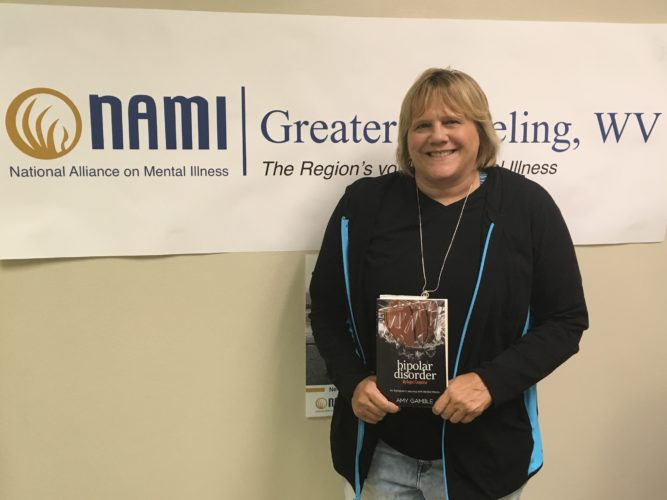 "Photo by Betsy Bethel Amy Gamble of Sherrard holds her self-published book, ""Bipolar Disorder: My Biggest Competitor"" in her Wheeling office of the National Alliance on Mental Illness."