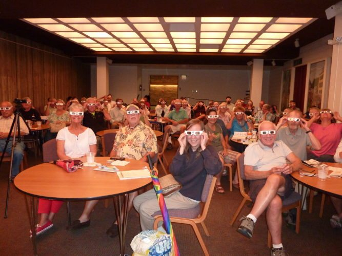Photo by Linda Comins Ohio County Public Library patrons practice wearing special protective glasses for viewing Monday's solar eclipse. Astronomer Robert Strong of Wheeling presented a program at the library Thursday night to explain the science of the solar eclipse, share tips for safe viewing and debunk misconceptions about the event.