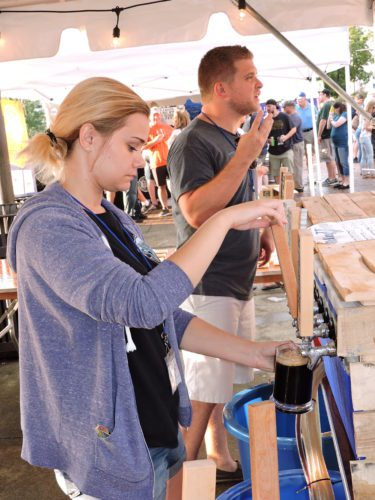 Photo by Casey Junkins Volunteering at the Wheeling Brewing Co. booth at Heritage Port Saturday during Mountaineer Brewfest are Brittany Bender and Drew Moore.