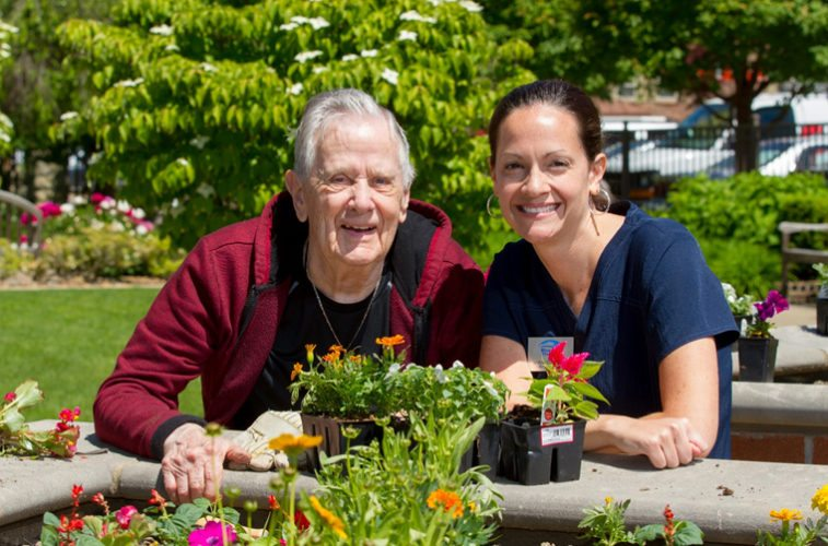 Photo Provided Resident Alvin Bandi and physical therapist Lindsey Dobbs add flowers to the Welty Home garden.