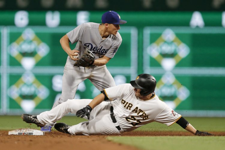 Pittsburgh Pirates' David Freese (23) is out at second on a fielders choice as Los Angeles Dodgers second baseman Chase Utley relays the ball to first on a ground ball by Josh Bell in the eighth inning of a baseball game, Monday, Aug. 21, 2017, in Pittsburgh. Pirates' Josh Harrison scored on the play, tying the game, as Bell was safe at first. (AP Photo/Keith Srakocic)