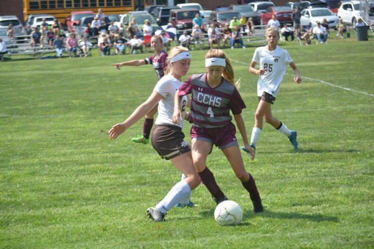 Photo by Josh Strope / Wheeling Central's Kenadee Wayt (4) tries to get around the defense of John Marshall's Damara Ferguson during prep soccer action Saturday in Glen Dale. The Maroon Knights won, 3-2.