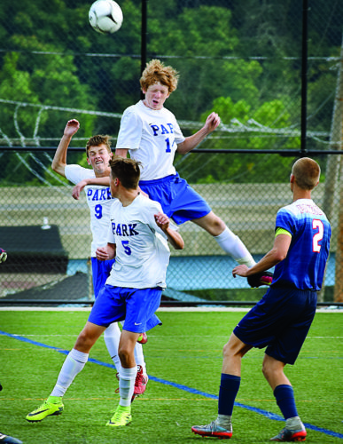 Photo by Scott McCloskey Wheeling Park's Phil White (14) goes high for a header above teammates Coleman Meredith (9) and Vincent Bauer on Tuesday against Parkersburg South.