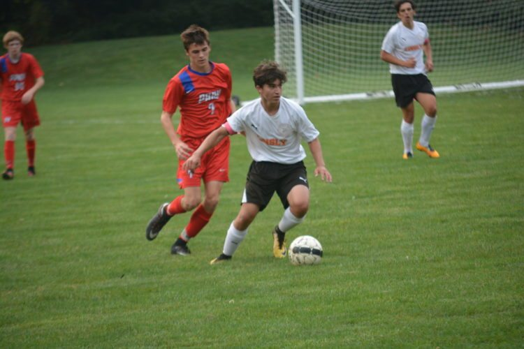Photo by Josh Strope Linsly's Matt Dudich, right, tries to keep the ball away from Wheeling Park's Bailey Mills (7) during Tuesday's game at Holloway Field in Wheeling.