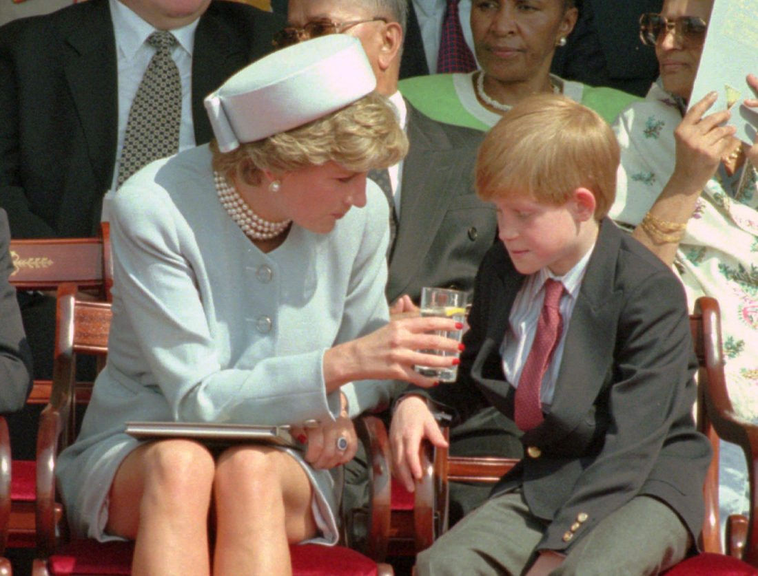 FILE - In this file photo dated Sunday May 7, 1995,  Princess Diana offers her son Prince Harry a drink of water during a open air ceremony to mark the 50th anniversary of VE Day, the end of World War II in Europe, in Hyde Park, London. Diana channeled Jackie Kennedy Onassis's style for an appearance on VE Day in 1995, appearing in a pale blue pillbox hat and matching suit. (AP Photo/Jacqueline Arzt, FILE)
