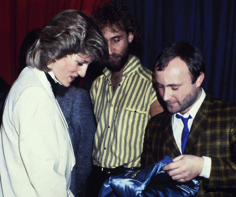 FILE - In this file photo dated Feb. 1984, Britain's Princess Diana talks with rock group Genesis with Mike Rutherford, center, and Phil Collins, right, in February 1984. The Princess surprised her fashion fans when she stepped out in a white dinner jacket, black trousers and silk, black bow tie to see the band Genesis perform a charity gig. (AP Photo, FILE)