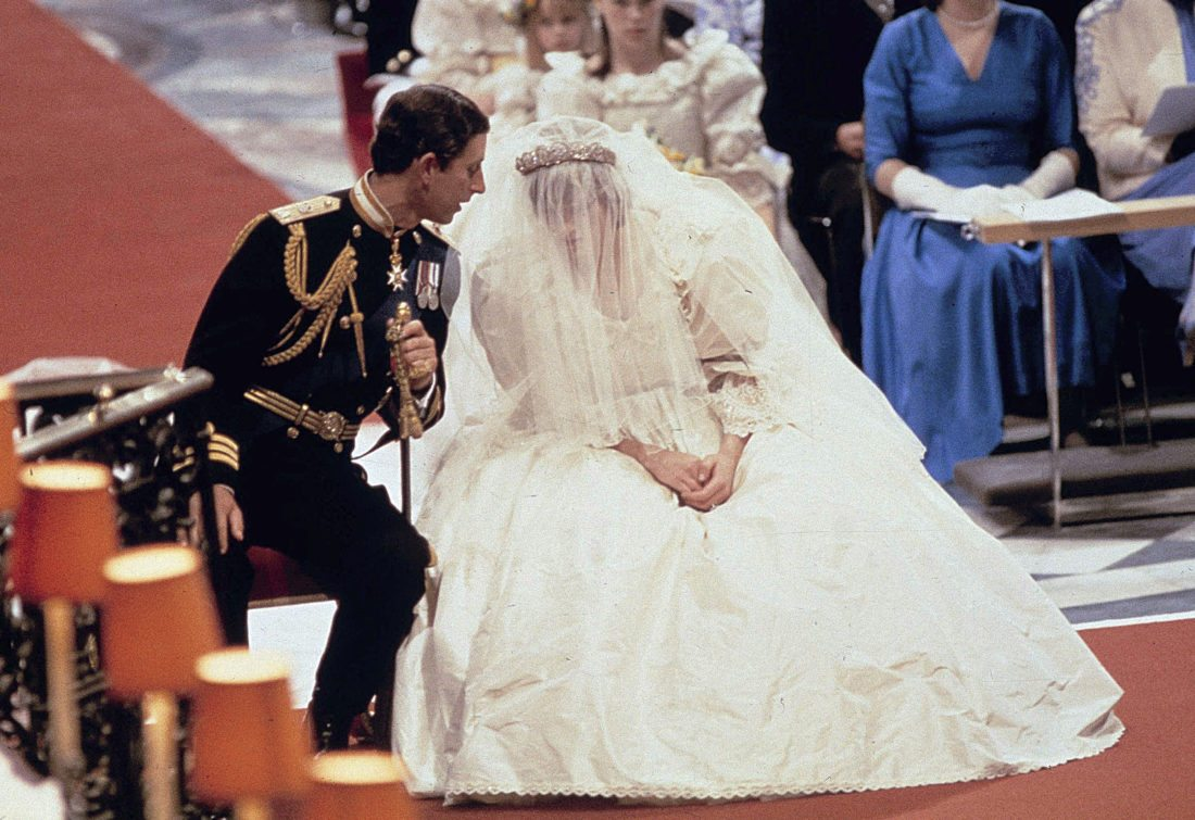 FILE - In this file photo dated July 29 1981, Britain's Prince Charles as he speaks with his bride Princess Diana, during their wedding ceremony in St. Paul's Cathedral, London. The wedding dress in 1981 delighted royal fans with its full silk taffeta gown and 25ft train by designers David and Elizabeth Emanuel. (AP Photo/File)