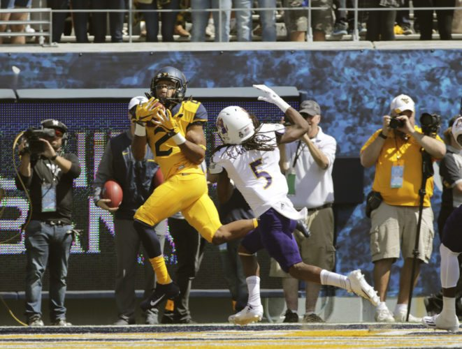 West Virginia wide receiver Ka'Raun White (2) catches a touchdown pass while being defended by East Carolina defensive back Corey Seargent (5) during the first half of an NCAA college football game, Saturday, Sept. 9, 2017, in Morgantown, W.Va. (AP Photo/Raymond Thompson)