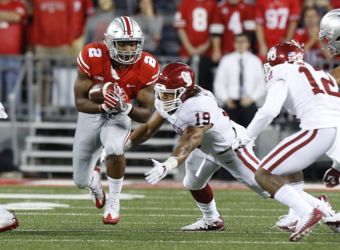 Ohio State running back J.K. Dobbins, left, runs the ball as Oklahoma linebacker Caleb Kelly tries to make the tackle during the first half of an NCAA college football game Saturday, Sept. 9, 2017, in Columbus, Ohio. (AP Photo/Jay LaPrete)