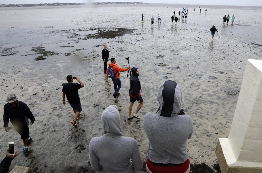 People walk out on to what is normally four feet of water in Old Tampa Bay, Sunday, Sept. 10, 2017, in Tampa, Fla. Hurricane Irma, and an unusual low tide pushed water out almost hundreds of yards. (AP Photo/Chris O'Meara)