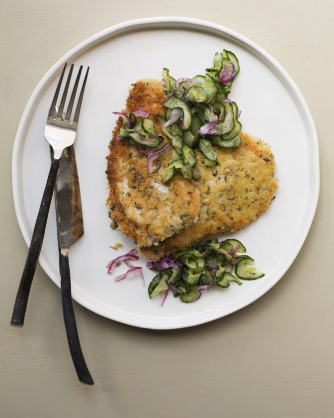 This June 2017 photo shows pork schnitzel with cucumber salad in New York. Schnitzels are often made with veal or chicken, but pork is a great alternative. Pounding out the cutlets makes them even tenderer and thinner, so they cook up quickly, perfect for a weeknight meal. (Sarah E Crowder via AP)