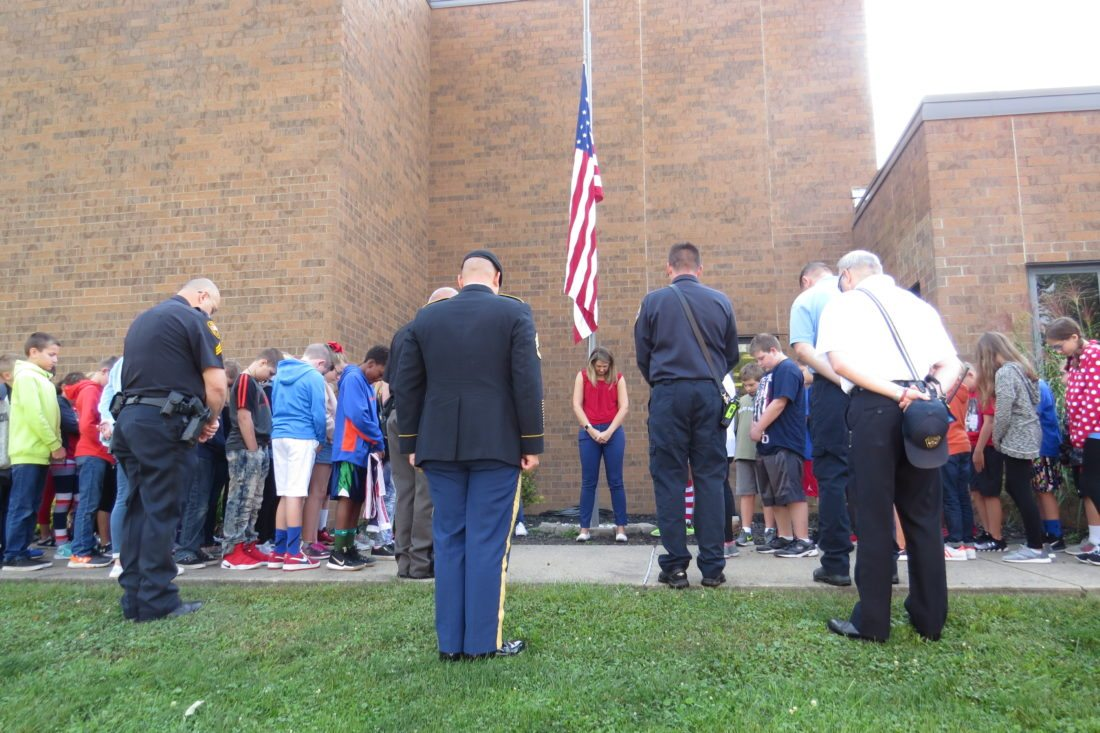 Photo Provided Standing at the base of the flagpole, Woodsdale Elementary School Principal Ashlea Minch leads a moment of silence in remembrance of the victims of 9-11 with her students, staff and members of the Wheeling Police and Fire departments in attendance.