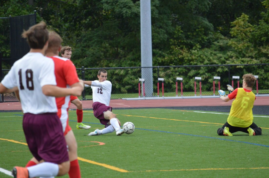 Photo by Kyle Lutz Angelo Gentile (12) slides as he makes a shot attempt on goal as Union Local goalkeeper Justin Fuhr defends.  Gentile went on to score in the Maroon Knights  victory.