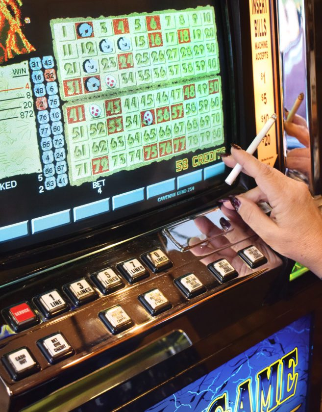 Photo by Scott McCloskey A patron smokes while playing a slot machine at a local limited video lottery parlor.