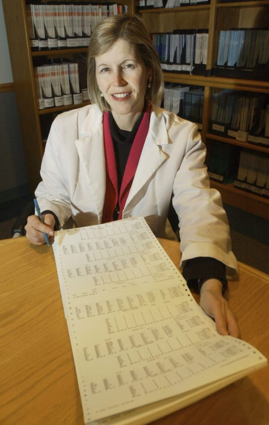 FILE - In this Dec. 12, 2002 file photo, Dr. JoAnn Manson poses with a printout from a study she directed on hormone replacement therapy for women at her office in Boston. In research results released on Tuesday, Sept. 12, 2017, Manson said hormones may be appropriate for some women when used short-term to relieve hot flashes and other bothersome menopause symptoms. (AP Photo/Elise Amendola)