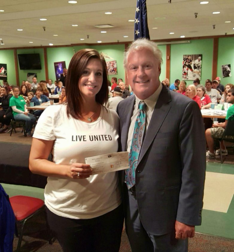 Photo by Joe Lovell Jessica Rine, associate director of the United Way of the Upper Ohio Valley, accepts a $10,000 check Wednesday from Jim Bordas of the Bordas & Bordas law firm in Wheeling.