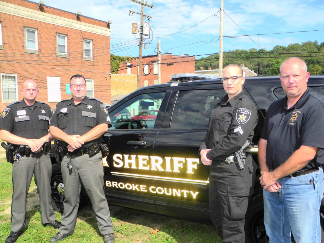 Photo by Warren Scott Brooke County Sheriff Larry Palmer, right, recognizes the efforts of three deputies who responded to Monday's fire at the former Genpak building and saved the lives of two juveniles believed to be responsible for the blaze. With him, from left, are Deputies Shane Siranovic, Tim Robertson and Kristen Richmond.