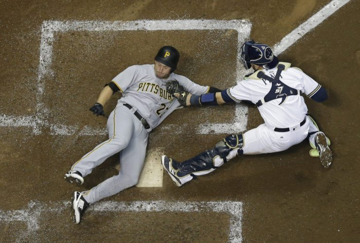 Milwaukee Brewers catcher Manny Pina tags out Pittsburgh Pirates' David Freese at home during the fourth inning of a baseball game Wednesday, Sept. 13, 2017, in Milwaukee. Freese tried to score from third on a long fly ball hit Elias Diaz. (AP Photo/Morry Gash)