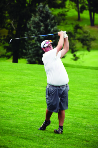 Photo by Seth Staskey Wheeling Central's Derrick Harrison watches his fairway shot during the OVACChampionship Thursday.