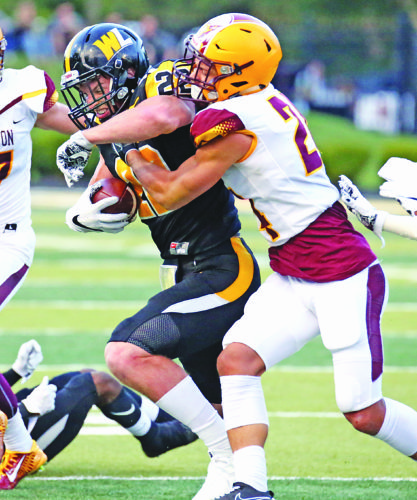 Photo by Alex Kozlowski West Liberty's Ian Kelly runs the ball as Charleston's Jonte Pooler goes for the tackle.