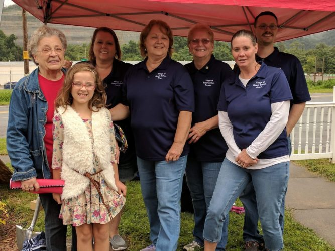 Photo Provided Assisting in burying a time capsule in Beech Bottom in celebration of the community's 100th anniversary, from left, are Mayor Becky Uhlly, Gracie Sheperd, Councilwoman Sharon Jordan, Florence Cronin, Councilwoman Debbie Murdock, Recorder Linda Dowell and Councilman Greg Sheperd.