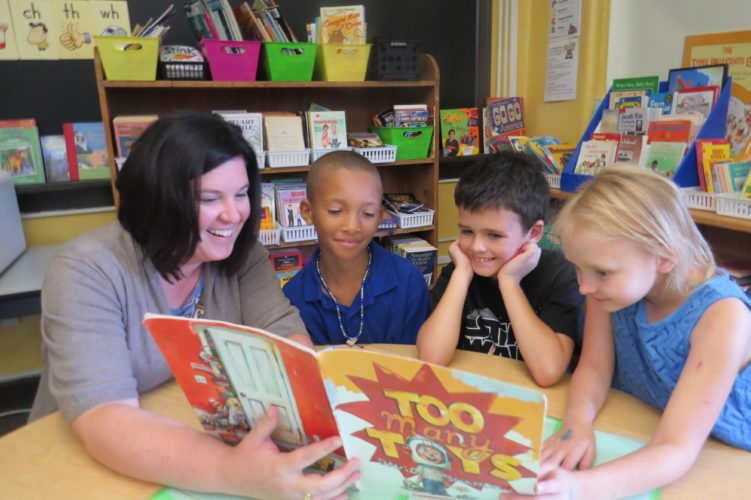 Photo Provided Madison Elementary School reading intervention specialist Melanie Riddle reads to students, from left, CaVohn Demello, Aaron Plecenik and Kaleigh Backus. Riddle is the chairperson of the Ohio County chapter of Read Aloud West Virginia.