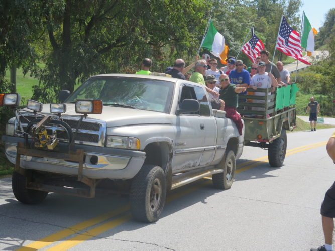 Photo by Alec Berry A truck decorated in Irish flags delivers a group of people to the start of the course.