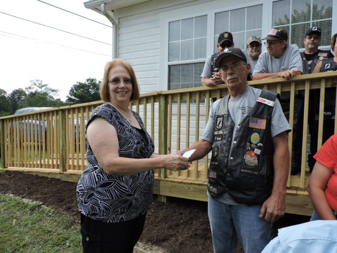 Photo by Janell Hunter Belmont County Military Veterans Museum Director Kim Kuthy receives an $800 donation from American Legion Riders Post 52 of Bellaire Ride Capt. Bruce Harris.