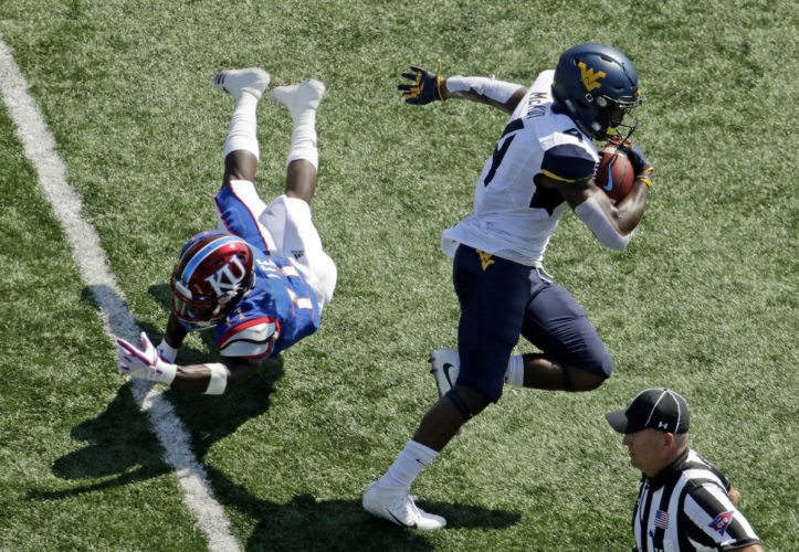 West Virginia running back Kennedy McKoy (4) gets past Kansas safety Mike Lee (11) to score a touchdown during the first half of an NCAA college football game Saturday, Sept. 23, 2017, in Lawrence, Kan. (AP Photo/Charlie Riedel)