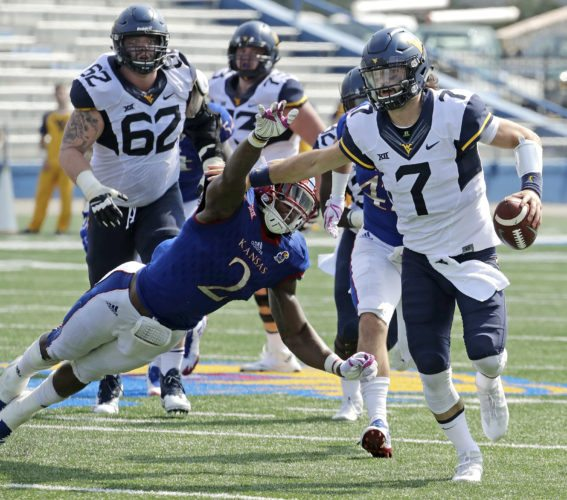 West Virginia quarterback Will Grier (7) evades Kansas defensive end Dorance Armstrong Jr. (2) as he runs for a first down during the second half of an NCAA college football game Saturday, Sept. 23, 2017, in Lawrence, Kan. West Virginia won 56-34. (AP Photo/Charlie Riedel)