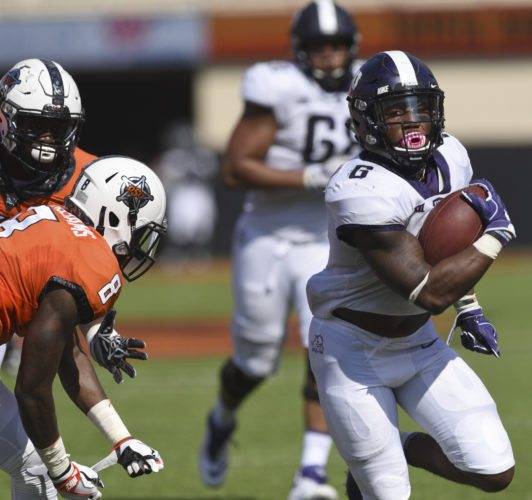 TCU running back Darius Anderson, right, break away from Oklahoma State defensive end Tralund Webber, left, and safety Za'Carrius Green to score a touchdown during the first half of an NCAA college football game in Stillwater, Okla., Saturday, Sept. 23, 2017.(AP Photo/Brody Schmidt)