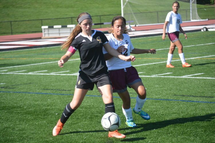 Photo by Josh Strope Wheeling Central's Abigail Gerney (12) and Crestview's Kassity Miller (4) battle for possession during Saturday's game at Bishop Schmitt Field.