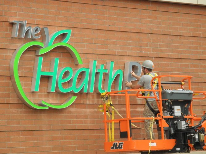 Photo by Casey Junkins A contractor applies The Health Plan's logo to the Main Street side of the company's new headquarters under construction in downtown Wheeling.