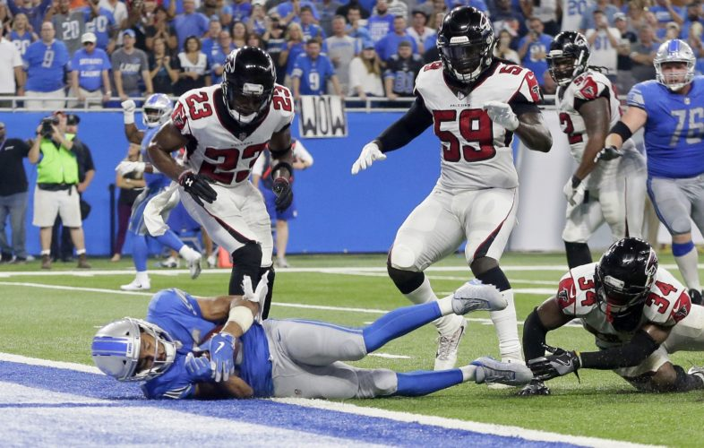 Detroit Lions wide receiver Golden Tate, bottom left, falls into the end zone for a 1-yard touchdown reception during the second half of an NFL football game against the Atlanta Falcons, Sunday, Sept. 24, 2017, in Detroit. The replay official reviewed the score ruling and the play was reversed. (AP Photo/Duane Burleson)