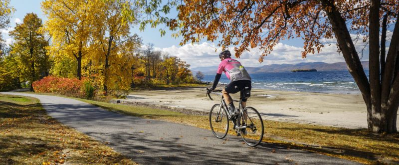 In this Oct. 19, 2016 photo provided by Local Motion, a man cycles along the Island Line Rail Trail in Burlington, Vt. Viewing fall foliage while walking or running one of New England's many scenic trails is a fun and healthy way to experience autumn. (Local Motion via AP)