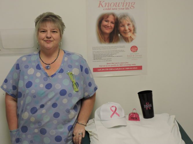 Photo by Alan Olson Registered nurse Cindy Wade displays breast cancer awareness materials in a patient room at Wheeling Health Right.