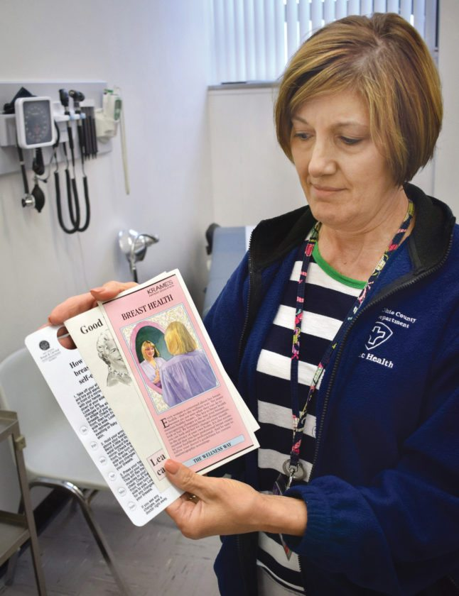 Photo by Scott McCloskey Wheeling-Ohio County Health Department registered nurse Maggie Sall displays several brochures regarding breast cancer awareness that the department can provide to clients.