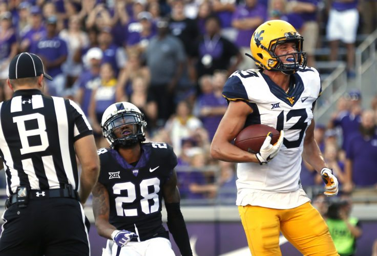 West Virginia wide receiver David Sills V (13) scores on a touchdown pass as TCU cornerback Tony James (28) looks on during the second half of an NCAA college football game Saturday, Oct. 7, 2017, in Fort Worth, Texas. TCU won 31-24. (AP Photo/Ron Jenkins)