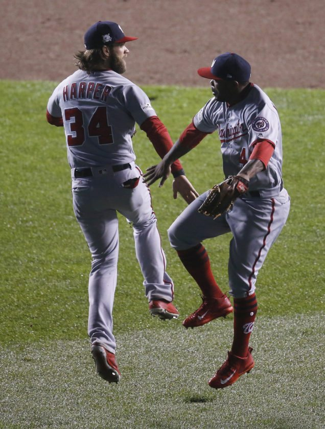 Washington Nationals' Bryce Harper (34) and Howie Kendrick (4) celebrate after Game 4 of baseball's National League Division Series against the Chicago Cubs, Wednesday, Oct. 11, 2017, in Chicago. The Nationals won 5-0. (AP Photo/Charles Rex Arbogast)