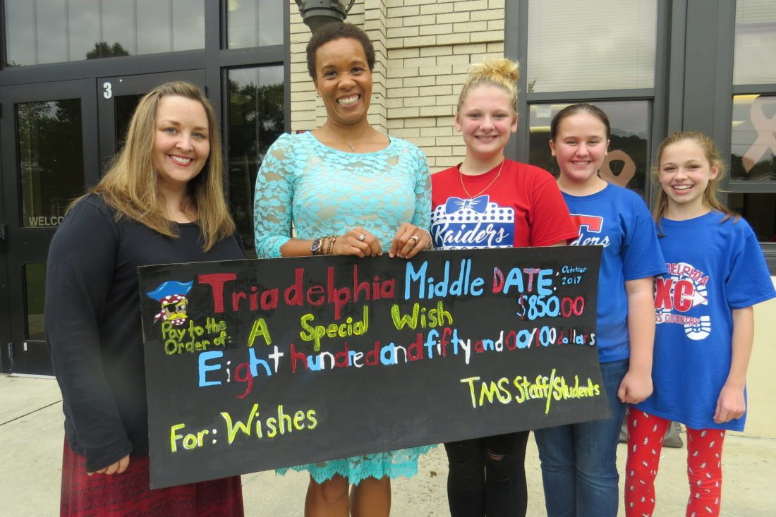 Photo Provided Pictured from left are Triadelphia Middle School teacher Erica Alexander, A Special Wish executive director Alicia Freeman, and students Gabby Means, Ava Sunseri and Isabella Border with a makeshift check for $850 to help the organization grant wishes to local children battling cancer and other life-threatening diseases.