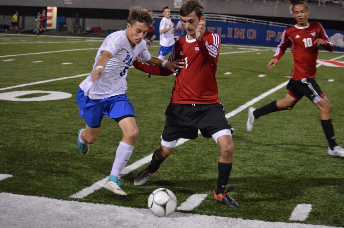 Photo by Cody Tomer Wheeling Park's Vincent Bauer (left) battles for possession with Weir's Luke Tenaglio during Thursday's Senior Night contest.